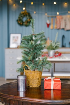 Abeto artificial en una cesta de mimbre se encuentra sobre una mesa en la sala de estar