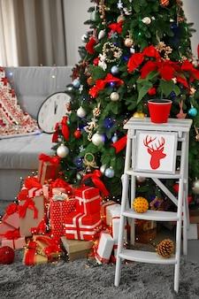 Abeto de navidad con regalos en salón