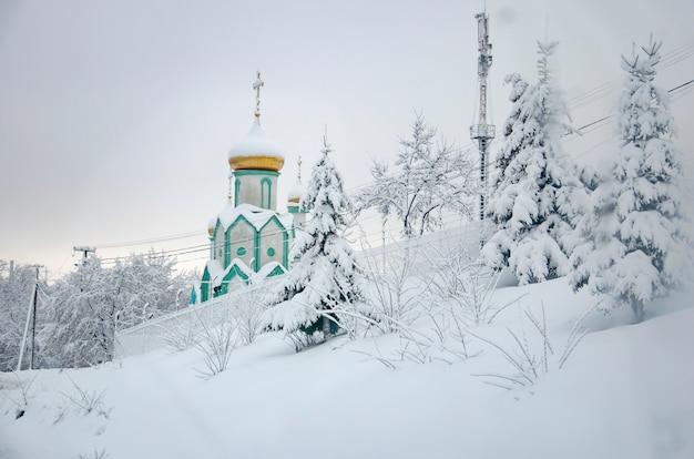 Abeto nevado helado y una iglesia con cúpula dorada en las montañas de los cárpatos, ucrania