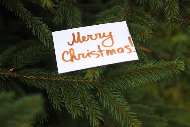Abeto con tarjeta de papel en la rama. inscripción de feliz navidad.