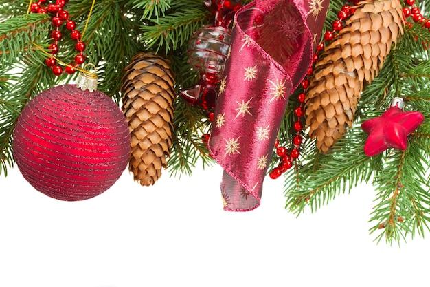 Abeto verde y adornos navideños rojos con borde de conos
