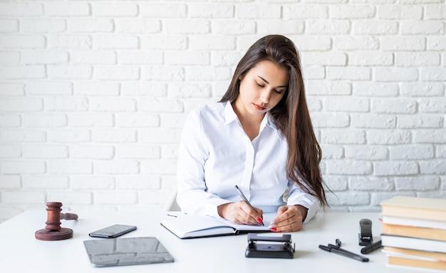 Abogada joven trabajando tomando notas en el cuaderno sobre fondo de pared de ladrillo blanco