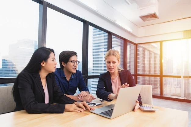 La abogada o asesora financiera sonriente muestra un contrato y un acuerdo de seguro para clientes multirraciales de pareja en la oficina, bienes raíces y concepto de acuerdo de compra de inversión