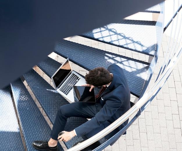 Abogado de alto ángulo con laptop y tablet en escaleras