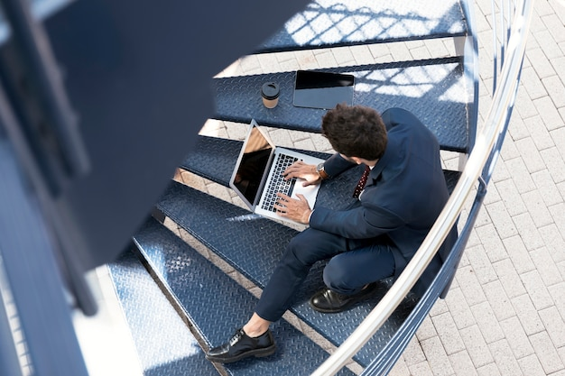 Abogado de alto ángulo con laptop, tableta y café