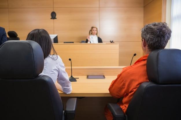 Abogado y cliente escuchando al juez