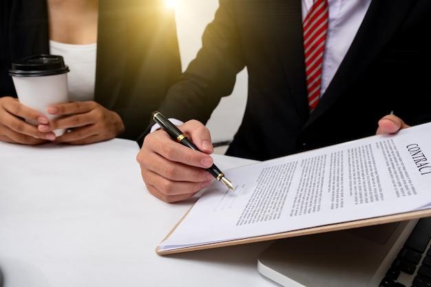 Abogado detalle de un juez sentado en su escritorio, estudiando nuevas leyes y legislación y tomando notas. enfoque selectivo.