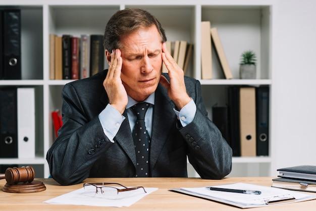 Abogado maduro con dolor de cabeza sentado en la sala del tribunal