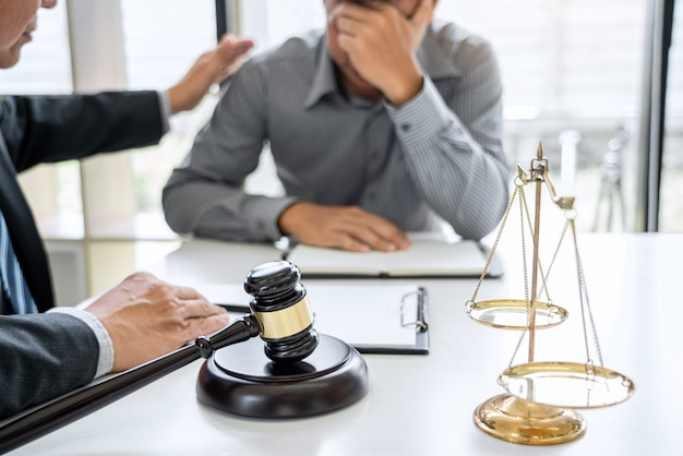 El abogado masculino que trabaja en la sala del tribunal se reúne con el cliente y consulta los documentos del contrato.