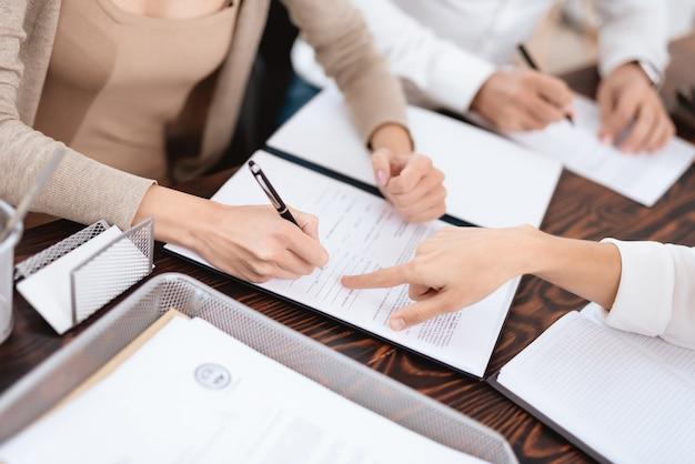 El abogado muestra dónde debe firmar el certificado de divorcio.