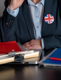Abogado o empleado de oficina o funcionario cerca de su lugar de trabajo con la bandera de gran bretaña en un icono de chaqueta