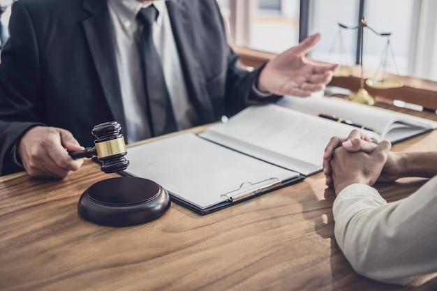 Un abogado o un juez consultan tener una reunión de equipo con una empresaria.