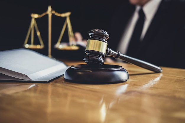 Abogado o juez que trabaja con documentos contractuales, libros de leyes y martillo de madera sobre una mesa en la sala de audiencias