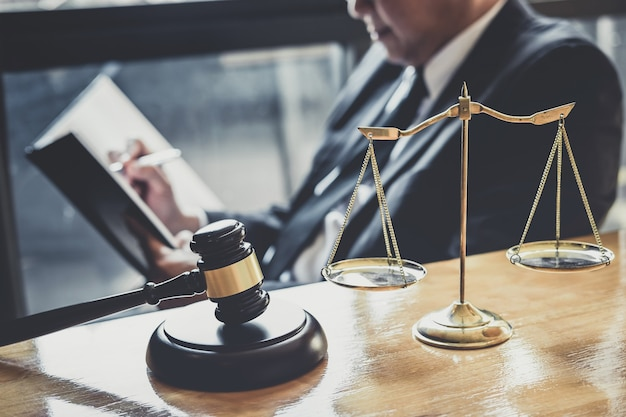 Abogado o juez de sexo masculino que trabaja con documentos contractuales, libros de derecho y mazo de madera en la mesa en la sala del tribunal
