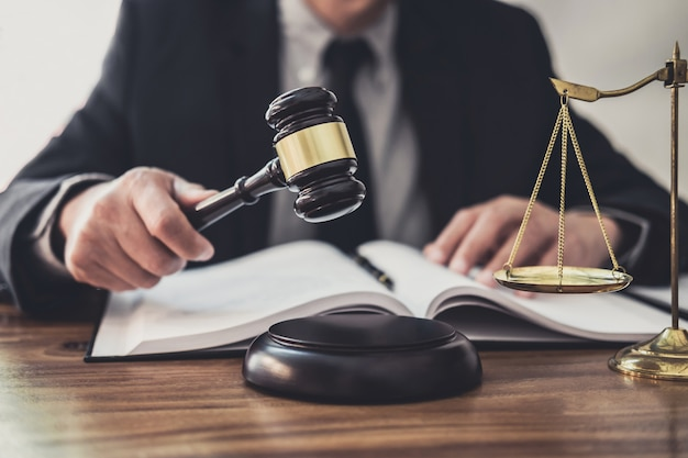 Abogado o juez de sexo masculino que trabaja con documentos contractuales, libros de leyes y martillo de madera sobre una mesa en la sala de audiencias