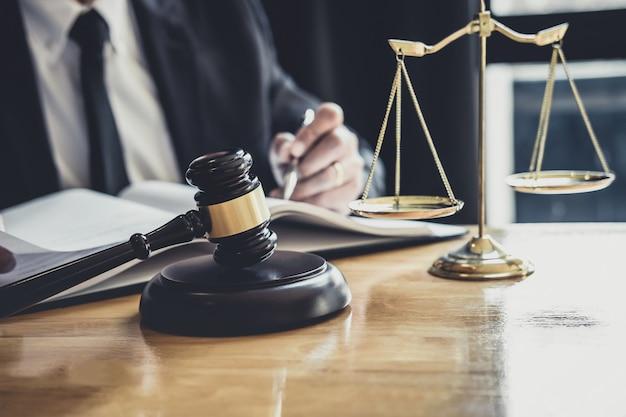 Abogado o juez varón trabajando con papeles contractuales.