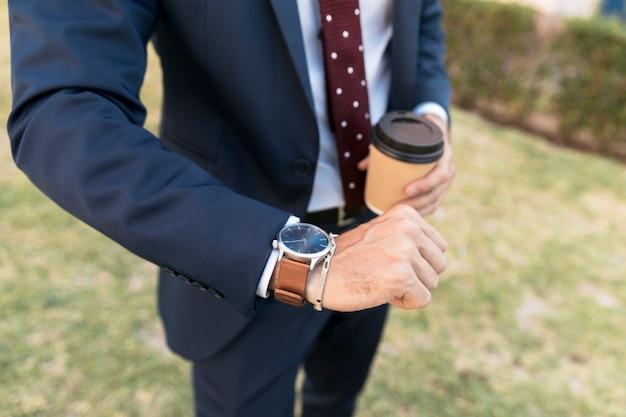 Abogado de primer plano con café mirando su reloj