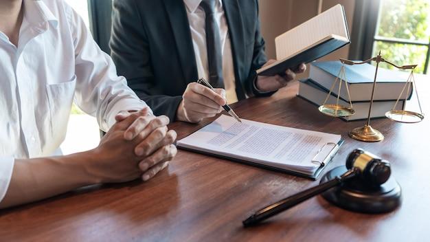 Abogado que trabaja con el cliente discutiendo sobre legislación legal en la sala del tribunal