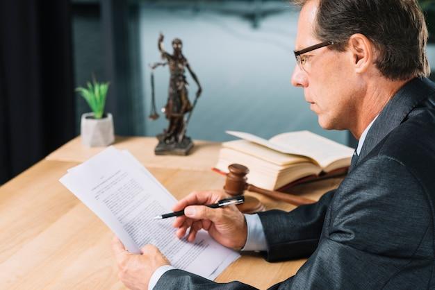 Abogado de sexo masculino maduro que sostiene la pluma en la mano que controla el documento de papel en sala de tribunal