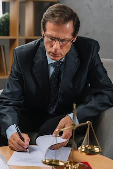 Abogado de sexo masculino maduro serio que firma el contrato con la pluma en el cuarto del tribunal