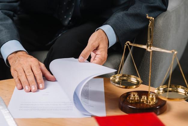 Abogado de sexo masculino que da vuelta a las páginas del documento en el escritorio con escala de justicia.