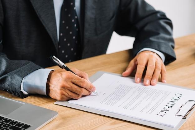 Abogado de sexo masculino que firma el contrato con la pluma en el tablero