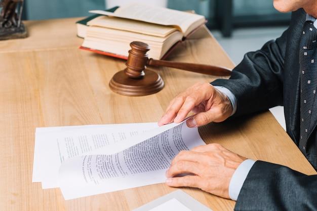 Abogado de sexo masculino que lee documentos en el escritorio de madera