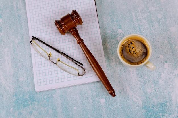 Abogados juez escritorio con jueces de madera martillo una taza de café, cuaderno de gafas de lectura