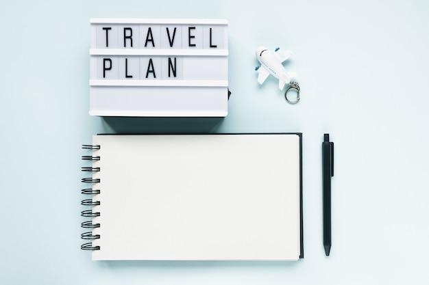 Abra el bloc de notas, el avión, la pluma y el texto plan de viaje sobre fondo azul. viajar a hacer lista, vacaciones y vuelos internacionales durante el concepto de coronavirus covid-19. endecha plana, espacio de copia, maqueta