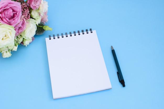 Abra un bloc de notas en blanco en la espiral sobre fondo azul con un bolígrafo azul oscuro y un ramo de diferentes flores frescas