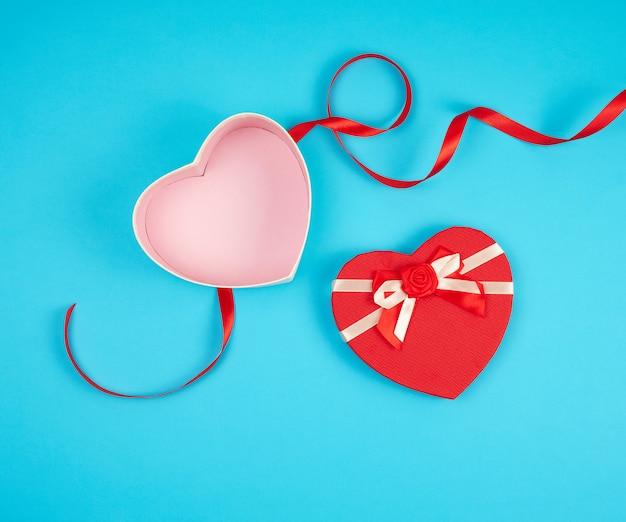Abra la caja de regalo en forma de corazón rojo con un arco sobre un fondo azul