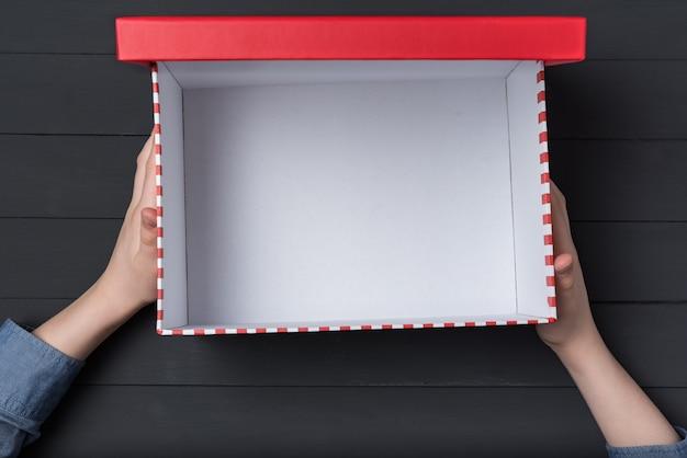 Abra la caja roja vacía en manos de los niños sobre fondo negro.
