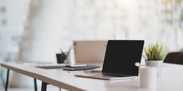 Abra la computadora portátil en blanco en el lugar de trabajo moderno con suministros de oficina y decoraciones