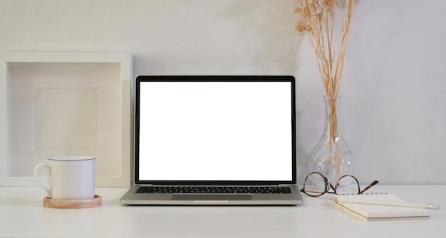Abra la computadora portátil de pantalla en blanco en la mesa de madera blanca