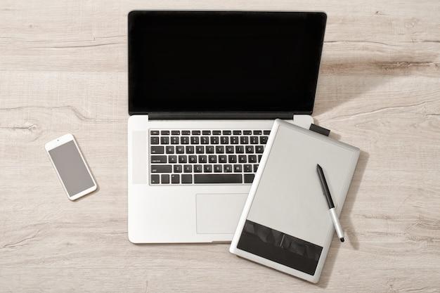 Abra la computadora portátil, tableta gráfica y teléfono inteligente en una mesa de luz, vista superior