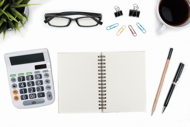 Abra el cuaderno espiral en blanco y la calculadora en la mesa de escritorio blanco