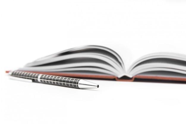 Abra el cuaderno con la pluma negra en el fondo blanco. aislado en blanco