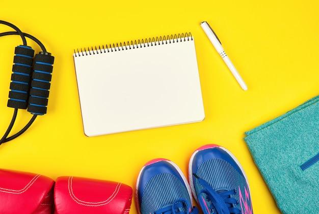 Abra el cuaderno vacío y la ropa deportiva femenina para deportes y fitness