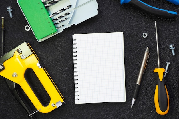 Abra el cuaderno y varias herramientas para reparación y construcción sobre un fondo negro de textura. copia espacio