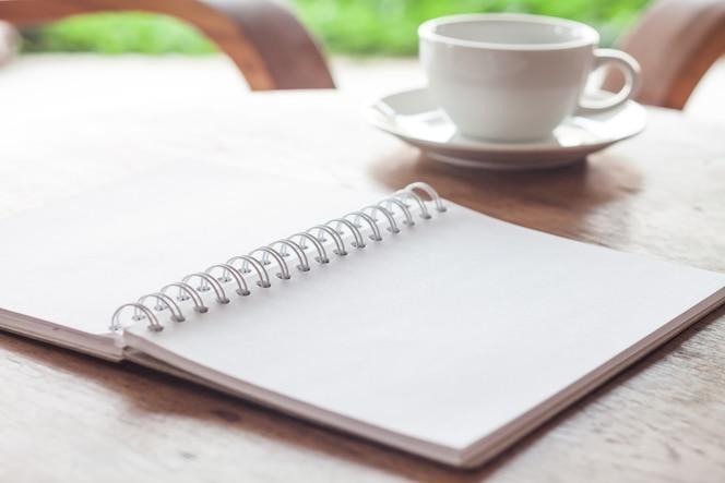 Abra el cuaderno blanco en blanco con la taza de café