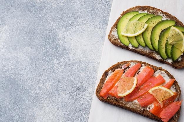 Abra los emparedados con espinaca y salmón de aguacate en una mesa gris. copia espacio