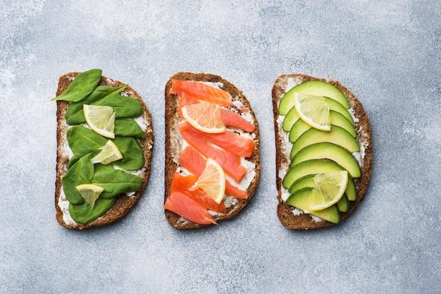 Abra los emparedados con espinaca y salmón de aguacate en una mesa gris.
