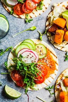 Abra las envolturas de tortilla vegana con camote, frijoles, aguacate, tomate, calabaza y brotes sobre fondo gris, plano. concepto de comida vegana saludable.
