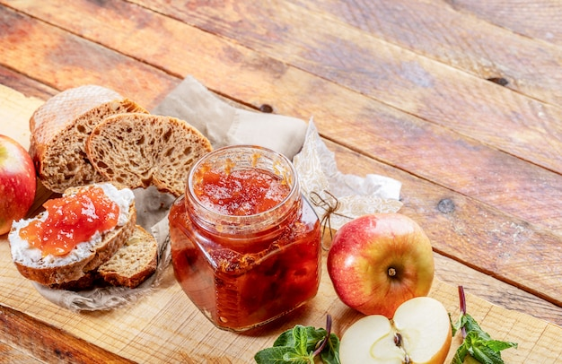 Abra el frasco de vidrio con mermelada de manzana, pan, untado con cuajada y mermelada de manzana