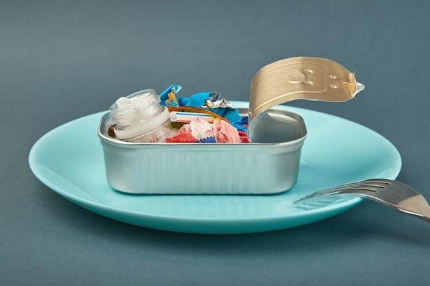 Abra la lata en el plato y el tenedor. residuos de plástico en lugar de peces en el interior. concepto de contaminación plástica del océano