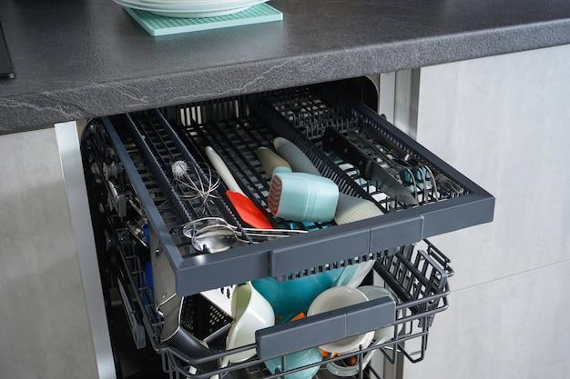 Abra el lavavajillas con platos limpios en la cocina del hogar, después del lavado.