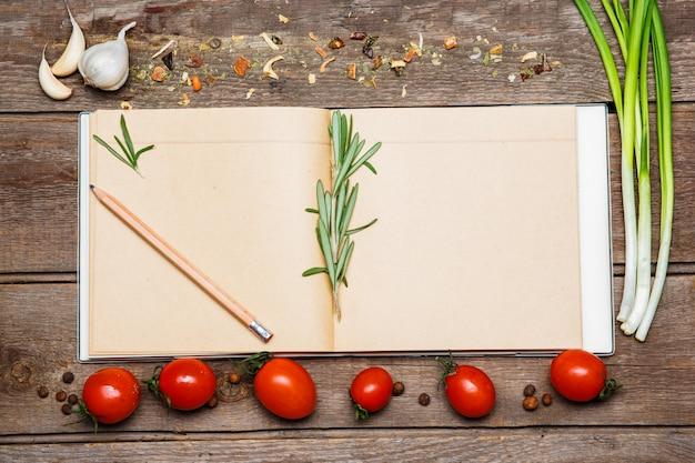 Abra el libro de recetas en blanco sobre fondo de madera marrón