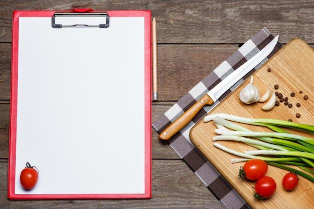 Abra el libro de recetas en blanco sobre madera marrón