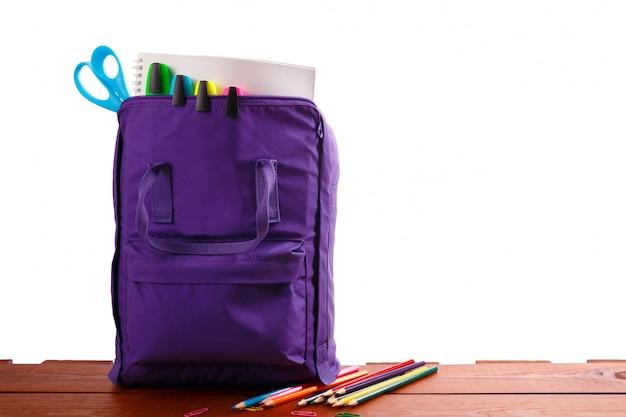Abra la mochila púrpura con útiles escolares en la mesa de madera. de vuelta a la escuela