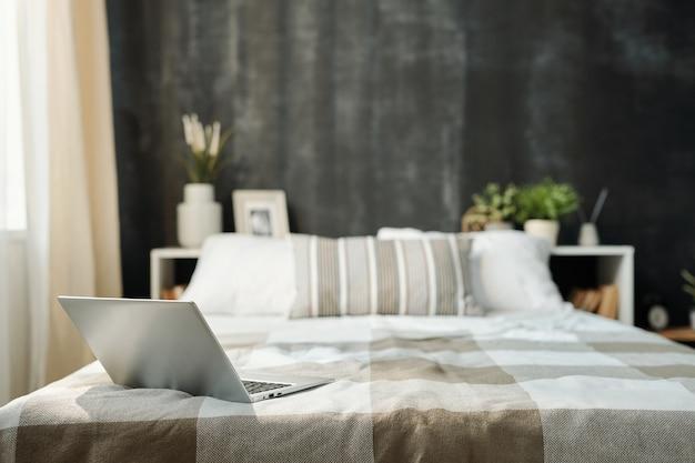 Abra el portátil en la cama cuidadosamente hecha con lino a cuadros a cuadros y un grupo de almohadas